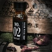 An Apothecary bottle of Vampfangs Fragance: No.2 Salem Witch Shop photographed in an actual Salem Witch Shop named Hex. A cracked, wooden board with an etched in skull. Smoking rose petals and some green moss complete the photo as accents.